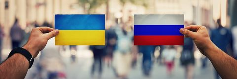 Ukraine vs russia. Two hands holding different flags, Russia vs Ukraine on politics arena over crowded street background. Future strategy, relations between royalty free stock images
