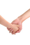 Two hands holding each other. Close-up studio shot of two hands holding each other Royalty Free Stock Images