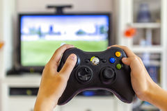 Two hands holding a game pad Stock Photos