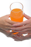 Two hands holding glass of orange fluid Stock Images