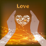 Two hands holding a heart on  gold background. Stock Images