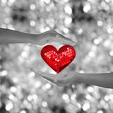 Two hands holding red heart shap on black and white bokeh Royalty Free Stock Photography