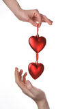 Two hands holding red hearts. Female hand giving red hearts and male hand catching them Stock Photography