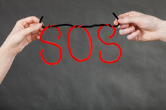 Two hands holding red SOS sign. Sadness, depression, troubles and very hard break up concept. Two hands holding red SOS sign Royalty Free Stock Images