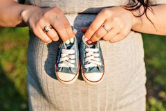 Hands holding sneakers for newborn royalty free stock photos