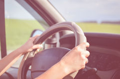 Two hands holding steering wheel inside car with. Closeup of two hands holding steering wheel inside car with blurred countryside green and blue background Stock Images