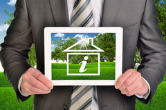 Two hands holding tablet pc with picture of house Stock Photos