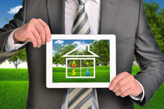 Two hands holding tablet pc with picture of house Royalty Free Stock Photo