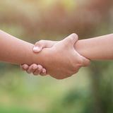 Two hands holding together. Help or support concept. On green bl Royalty Free Stock Photography