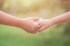 Two hands holding together. Help or support concept. On green bl Stock Photos