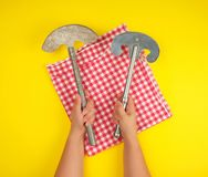 Two hands holding vintage sharp kitchen knives for meat and vegetables. Yellow background stock photography