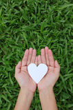 Two hands holding white heart Stock Photography