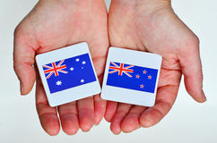 Two hands holds the national flags of Australia (R) and New Zeal Royalty Free Stock Photo