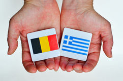 Two hands holds the national flags of Germany (L) and Greece (R) Stock Photo