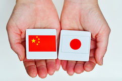 Two hands holds the national flags of the Republic People of Chi Stock Image
