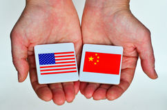 Two hands holds the national flags of the United States of Ameri Royalty Free Stock Photo