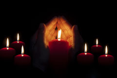 Two hands illuminated by  a candle in the darkness Stock Photos