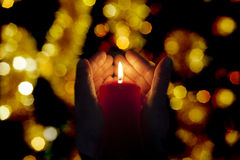 Two hands illuminated by  a candle in the darkness Royalty Free Stock Photos