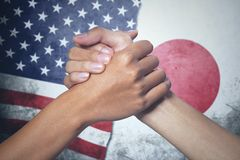 Two hands with Japan and United States flag. Closeup of two hands people posing partnership with Japan and United States flag in the background Stock Image