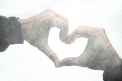 Two hands join to form a heart shape at snowfall Royalty Free Stock Images