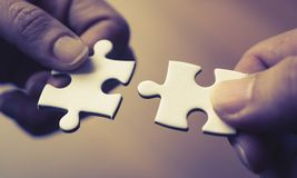 Two hands joining together two jigsaw. Puzzles Stock Photo