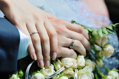 Two hands of just married couple holding each over. A closeup photo of two hands of just married couple holding each over with rings and flower near Stock Image