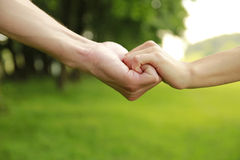 Two hands of a loving couple on nature Stock Photo
