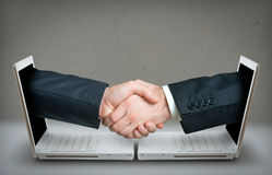 Two hands making a deal over internet. Over a gray wall Royalty Free Stock Image
