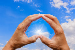 Two hands making a heart shape. With the light from the sun Royalty Free Stock Photography