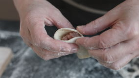 Two hands making meat dumplings. stock video footage