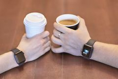 Two hands, male and female, both with equal electronic wrist watches, holding cups of coffee, white and black, on the wooden table. Date or friends meeting royalty free stock images