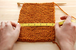 Two hands measuring knitting in inches Royalty Free Stock Photography