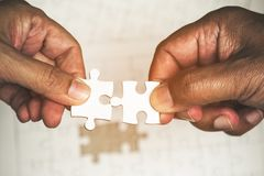 Two hands of men connecting the couple pieces of white puzzle. Teamwork success concept Royalty Free Stock Photography