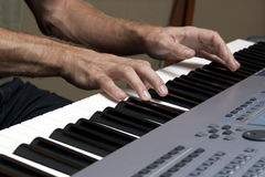 Two hands and music keyboards Stock Photography