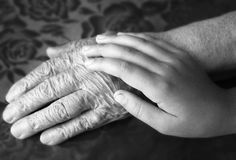 Two hands. Old and young. Child's hand on arm of an mature woman Stock Photography