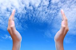 Two hands over the blue sky Royalty Free Stock Image
