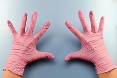Two hands in parchatka show all ten fingers. Two palms in pink rubber medical gloves on a blue background. They are located separately from each other, all five royalty free stock photos