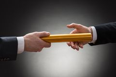 Two hands passing a golden relay baton. Close-up Of Two Businessman's Hand Passing A Golden Relay Baton royalty free stock image