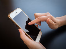 Two hands person holding and using smartphone. Close-up image of two hands person holding and using smartphone on black table Stock Photography