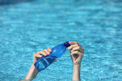 Two hands with plastic bottle of water  above surface of water Royalty Free Stock Photo