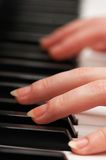 Two hands playing music. On the  piano Stock Photography