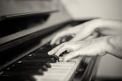 Two hands playing piano, shallow focus. Black and white Royalty Free Stock Image