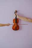 Two hands playing violin on purple background. Stock Photos