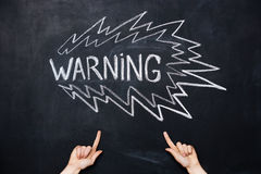 Two hands pointing at warning drawn on blackboard Stock Images