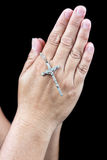 Two hands praying with a small silver crucifix Royalty Free Stock Image
