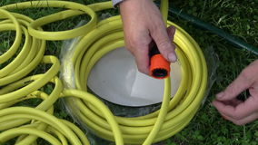 Two hands preparing water hose junction on grass. Two hands preparing water hose junction on the grass stock footage