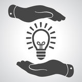 Two hands protecting black idea light lamp bulb icon on a grey b Royalty Free Stock Photos
