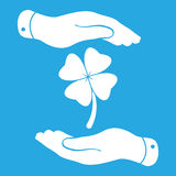 Two hands protecting clover with four leaves sign icon. on a blu Stock Image