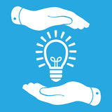 Two hands protecting white idea light lamp bulb icon on a blue b Stock Images