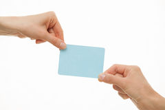 Two hands pull in different directions a blue paper card Royalty Free Stock Photos